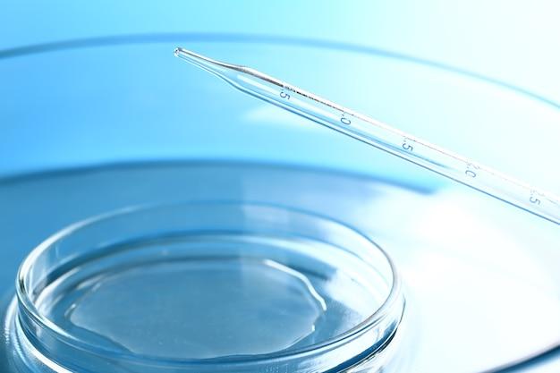 ピペットは、青い背景に対してサンプルを試験管に落とします。医療の抽象的な背景。化粧品のコンセプト
