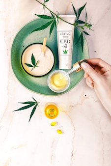 Pipette with cbd cosmetic oil in female hands with cosmetics, cream with cannabis and hemp leaves, marijuana.