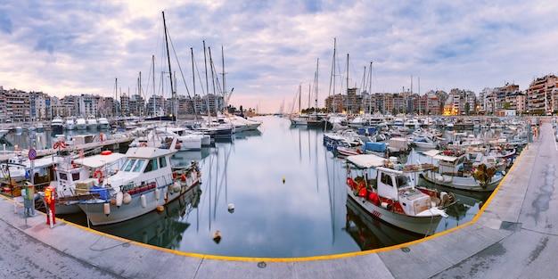 Пирей марина в утренний синий час. порт пирей, крупнейший греческий морской порт и один из крупнейших в средиземном море и европе, с древних времен служил портом афин, греции.