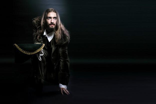 Пиратский человек с длинными волосами и бородой, сел на одно колено