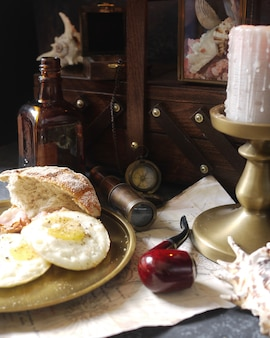 Pirate's breakfast: bacon and eggs, loaf of bread and rum