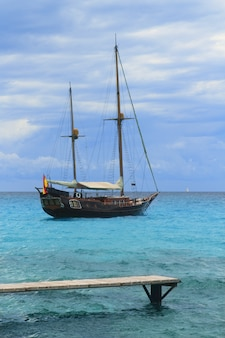 Pirates inspired wood sailboat anchored turquoise