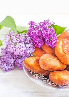 Piroshki - russian baked puff pastry with cabbage fillings and bouquet of lilacs. traditional russian cabbage stuffed baked pastry. lean pies with cabbage. beautiful homemade cakes with cabbage