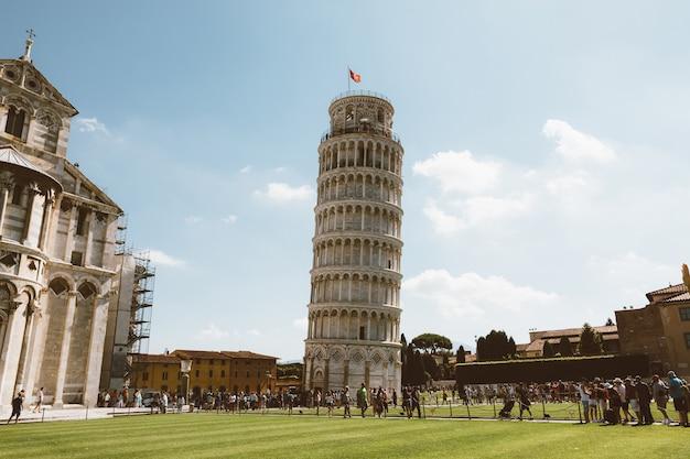 Пиза, италия - 29 июня 2018: панорамный вид на пизанскую башню или пизанскую башню (торре-ди-пиза) - колокольня на площади пьяцца-дель-мираколи, или отдельно стоящая колокольня собора города пизы