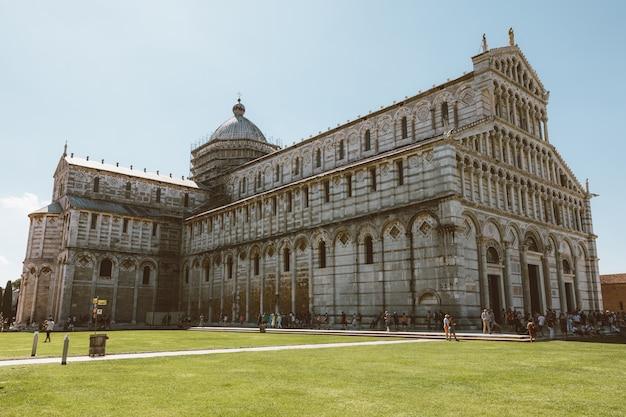 Пиза, италия - 29 июня 2018: панорамный вид на собор пизы и пизанскую башню на площади пьяцца-дель-мираколи. люди ходят и отдыхают на площади