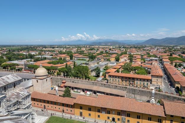 Пиза, италия - 29 июня 2018: панорамный вид на город пиза с историческими зданиями и горами вдали от пизанской башни. летний день и солнечное голубое небо