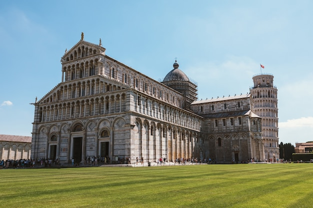 Pisa, italy - june 29, 2018: panoramic view of pisa cathedral and tower of pisa on piazza del miracoli. people walk and rest on square