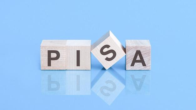 Pisaの言葉は、青いテーブルの上に横たわる木製の立方体、ビジネスコンセプトで作られています。 pisa-生徒の学習到達度調査プログラムの略