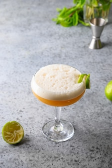 Pisco sour cocktail of whiskey, lime on grey.