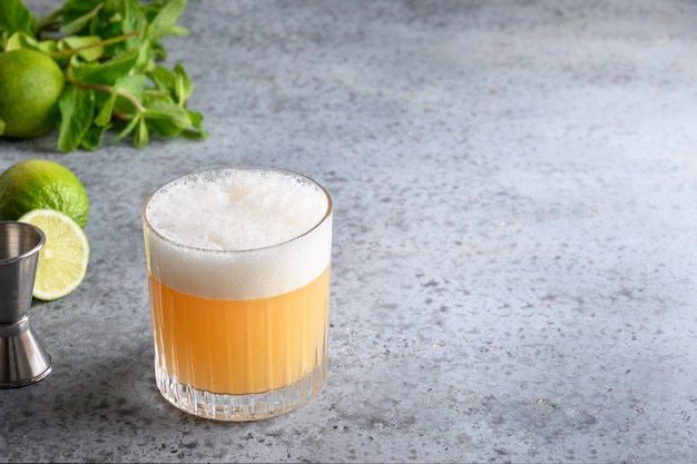 Pisco sour cocktail. whiskey with lime, egg white, honey on grey.