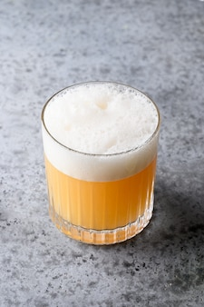 Pisco sour cocktail. whiskey with lime, egg white, syrup in glass on grey.