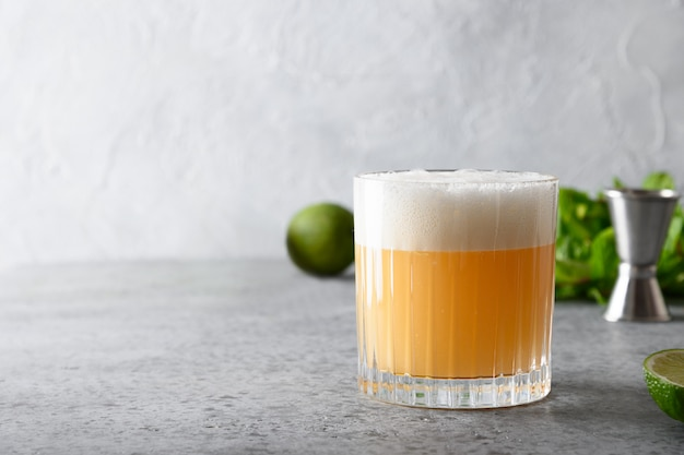 Pisco sour cocktail. whiskey with lime juice, sugar syrup and egg white in glass.