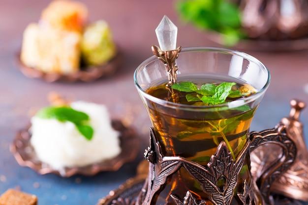 Чаша с турецкой сахарной ватой pismaniye и черный чай с мятой крупным планом