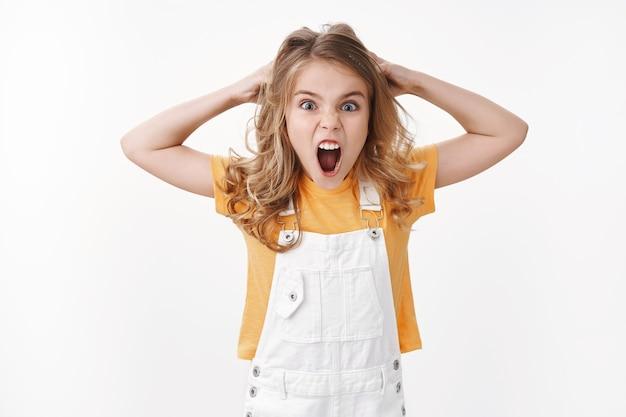 화난 금발의 어린 꼬마, 불평하는 소녀, 실망하고 화난 비명, 화가 나서 소리를 지르고, 기분이 상하고, 말다툼을 하고, 머리에서 머리를 잡아당기고, 찡그린다