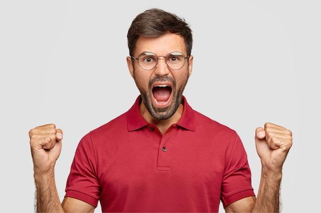 腹を立てて怒っている無精ひげを生やした男は拳で手を保つ