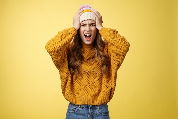 Pissed annoyed freaked-out girlfriend jealous screaming pissed insane caught boyfriend cheating hold hands head shouting angry frowning cringing disgust dissatisfied look camera, yellow background