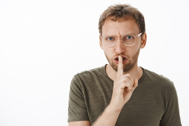Pissed and annoyed handsome man in glasses, green t-shirt frowning shushing with index finger over mouth demanding not talk during lesson over white wall