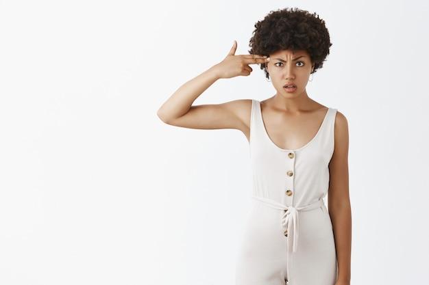Разозленная и разочарованная стильная девушка позирует у белой стены