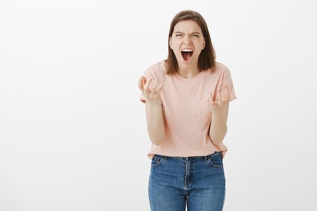 腹を立てて怒っている女性が手を握りしめ、誰かに怒って、憎しみを叫ぶ