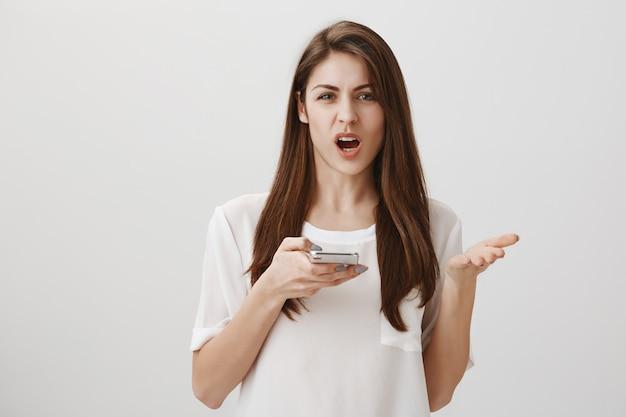 Раздраженная раздраженная женщина жалуется, держа мобильный телефон, выглядя разочарованным