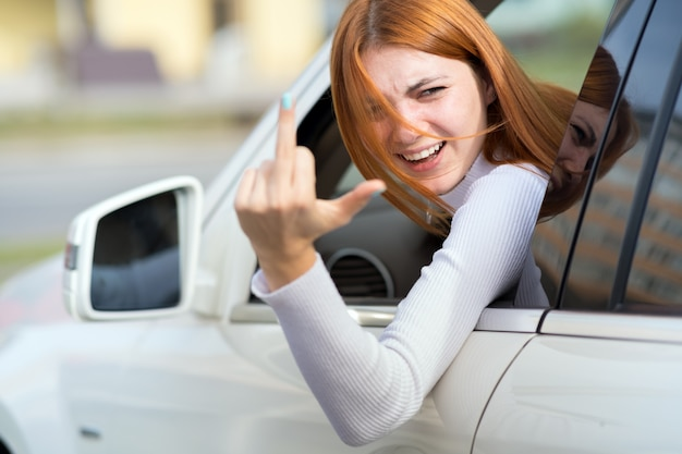 Pissed off displeased angry aggressive woman driving a car shouting at someone with middle finger gesture.