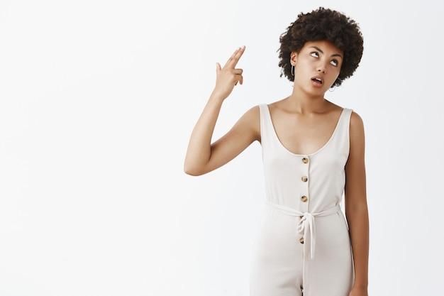 Ragazza alla moda incazzata e frustrata che posa contro il muro bianco