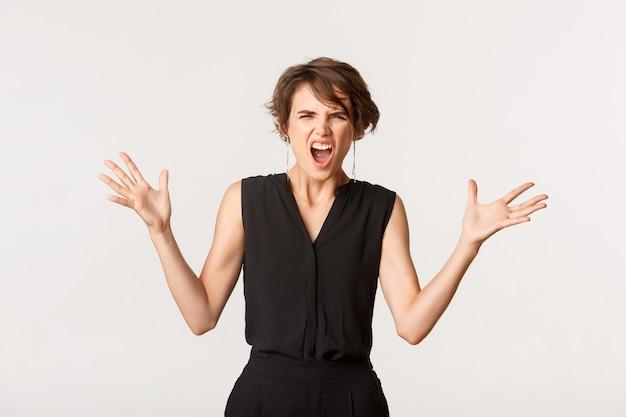 Разъяренная женщина кричит на кого-то и пожимает руки, спорит, выглядит безумной поверх белого.