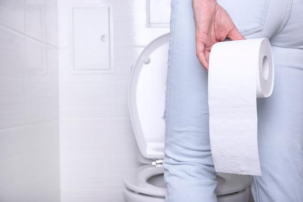 白いトイレで、手で白い紙のロールとトイレで下痢に苦しんでいる放尿女性