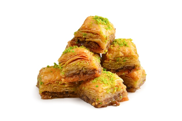 Pistachio baklava on a white wall. dessert.