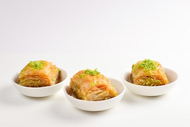 Pistachio baklava on a white wall. dessert.