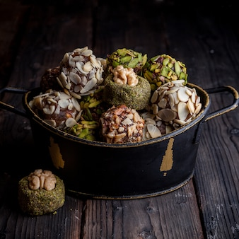 Pistachio cookies in a black pot on a dark wooden background. high angle view.