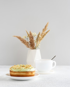 Pistachio donut and cup of coffe on a table with dry flowers in small minimalistic vase