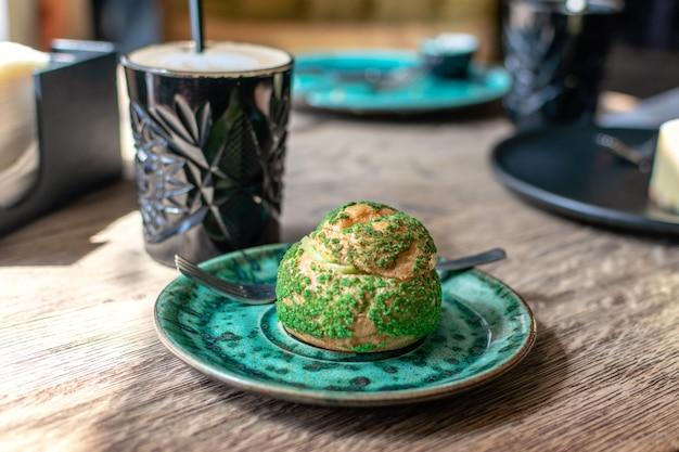 Pistachio eclair, profiterole in glaze