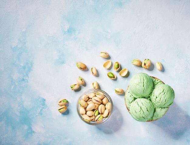 ターコイズブルーのテーブル、トップビューで背景に紙コップのピスタチオアイスクリーム