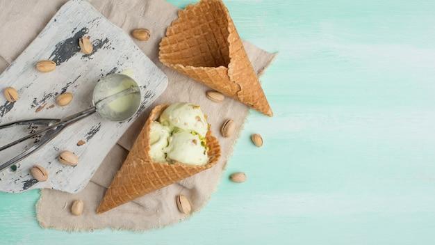 Фисташковое мороженое, посыпанное орехами, в двух классических мисках на светлом деревянном фоне