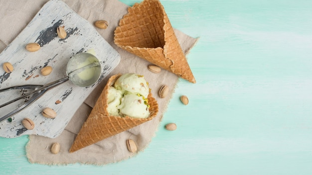 Pistachio ice cream, sprinkled with nuts, in two classic bowls on a light wooden background