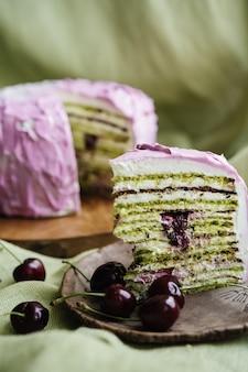 녹색 표면에 체리와 피스타치오 다층 케이크