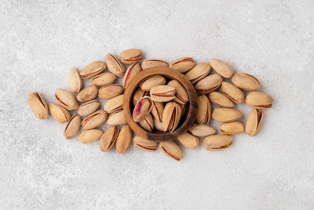 Pistachio nuts and bowl on marble table
