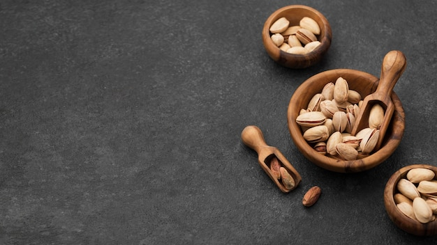 Pistachio nuts in bowls with wooden spoons copy space