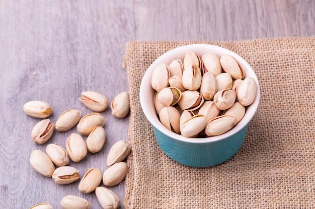 Фисташковые орехи в белой керамической миске на деревянном столе.