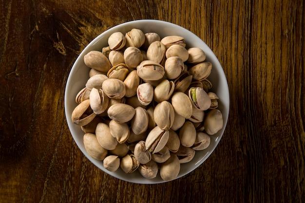 木の背景と白いボウルのピスタチオナッツ。