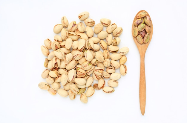 Pistachio nuts isolated on white background with wooden spoon.