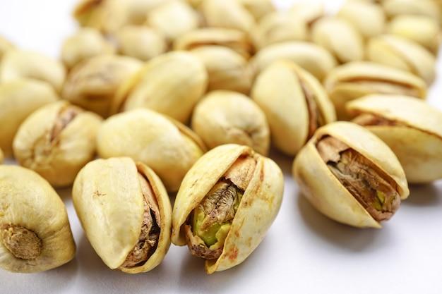 白い背景にピスタチオナッツ:健康的な食べ物の概念。