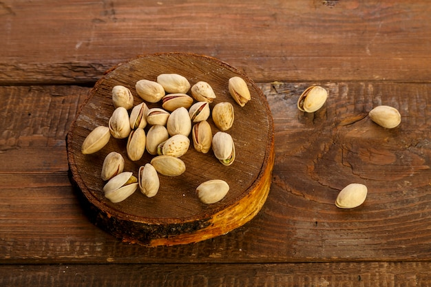 Pistachio nuts scattered on a round board on a wooden table.