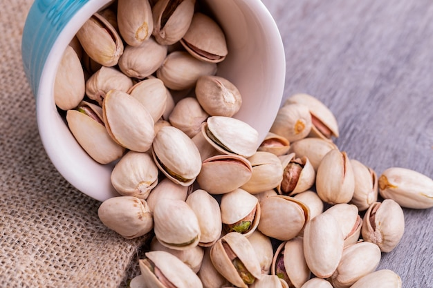 Pistachio nuts in a white ceramic bowl on a wooden table.