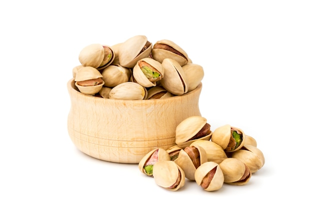 Pistachio nuts in a wooden plate on white