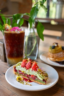 Pistachio strawberry tart filled with strawberry jam in white dish with lemon americano coffee