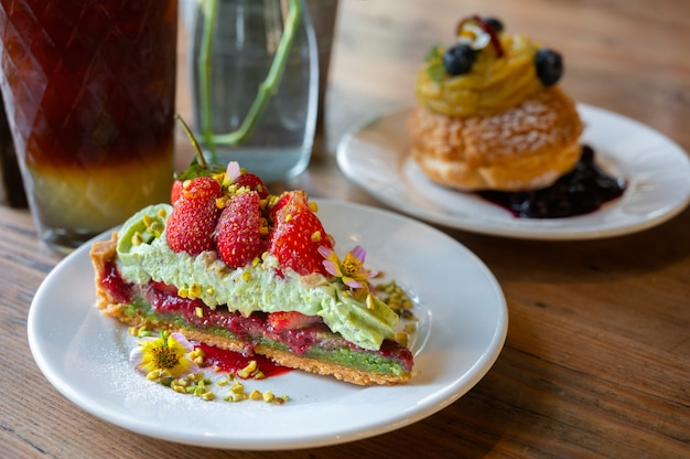 Pistachio strawberry tart filled with strawberry jam on wooden background.