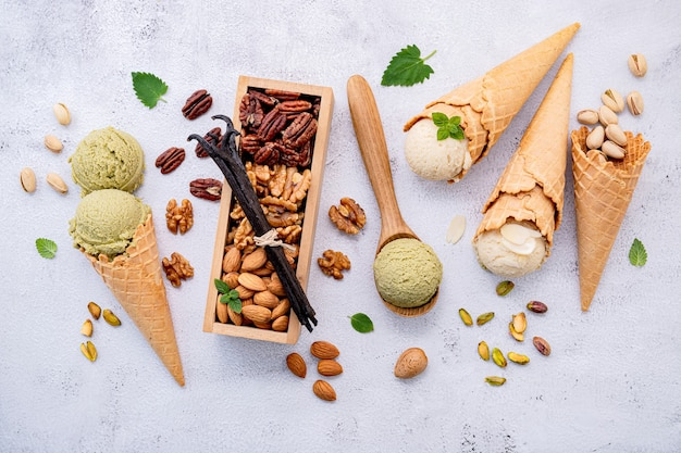 Pistachio and vanilla ice cream in bowl with mixed nuts setup on white stone background