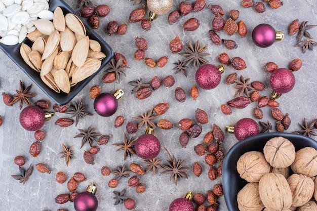 Фисташки, грецкие орехи и тыквенные семечки с шиповником и елочными шарами.